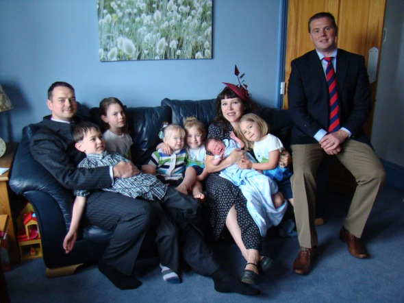 The whole family, with the Pastor on his couch