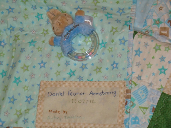 The text on the quilt reads: Daniel Feanor Armstrong 17-7-12