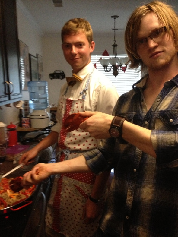 Guests from church (aka: playthings for our kids) Tripp manning the stove and Matthew, who was de-shelling the lobster claws